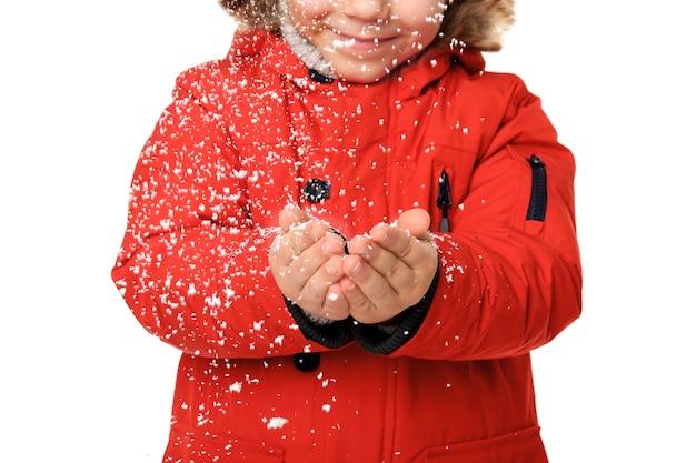 Ragazzino sveglio in vestiti caldi che gioca con la neve su superficie bianca, primo piano