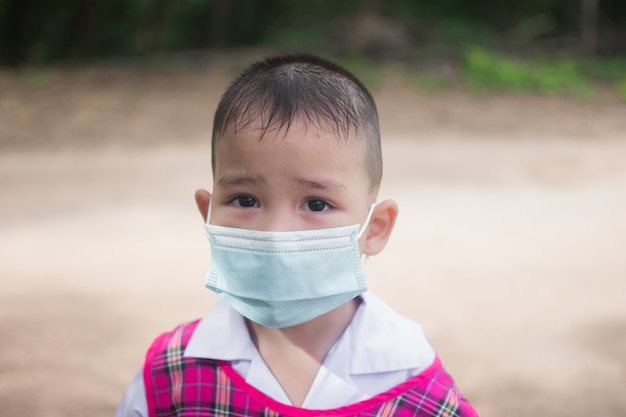 Simpatico ragazzino indossa una maschera per protezione coronavirus o covid 19.