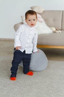 Un ragazzino carino con una camicia bianca sta giocando in un luminoso soggiorno accogliente