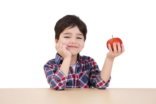 Ragazzino sveglio con la mela che si siede alla tavola, su fondo bianco