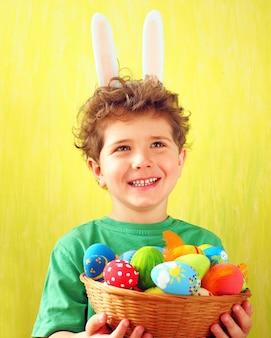 Ragazzino sveglio con orecchie da coniglio in testa e uova di pasqua colorate in un cesto di vimini nelle sue mani