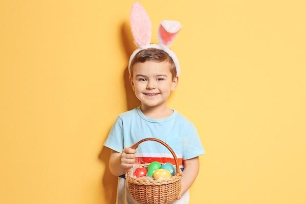 Ragazzino sveglio con le orecchie del coniglietto che tiene il cestino pieno delle uova di pasqua sul colore