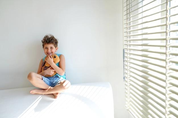 Un ragazzino sveglio con i capelli ricci si siede sul divano bianco con il suo cane giocattolo e sorride
