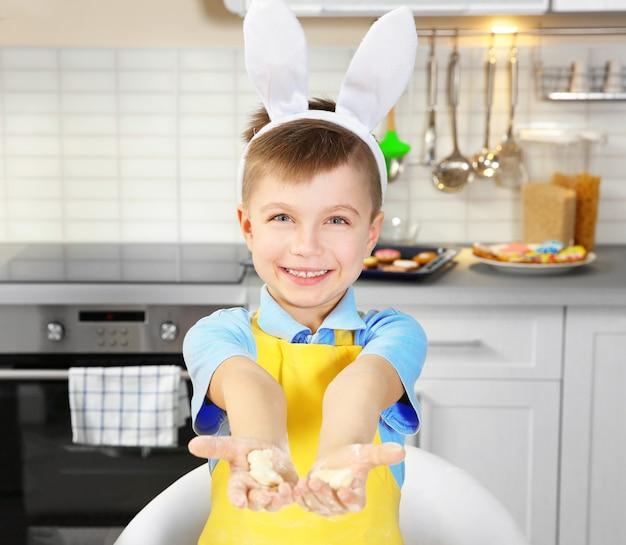 Ragazzino carino con i biscotti di pasqua in cucina