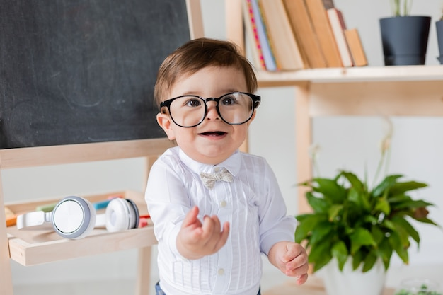 Un simpatico ragazzino con gli occhiali che sorride accanto alla lavagna e ai libri. educazione prescolare per bambini