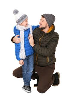 Ragazzino sveglio con il padre in vestiti caldi su superficie bianca. pronti per le vacanze invernali