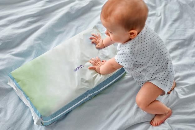 Ragazzino sveglio con un pacco di mutandine per pannolini sdraiato sul letto a casa. igiene dei bambini.