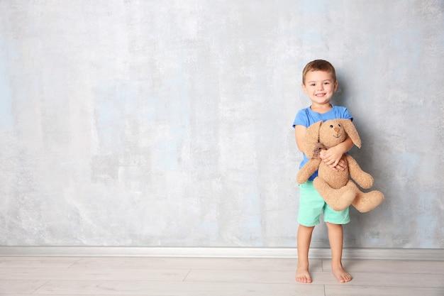 Ragazzino sveglio con il coniglietto del giocattolo vicino al muro grigio