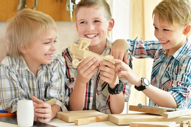 Ragazzini carini che lavorano con il legno in officina