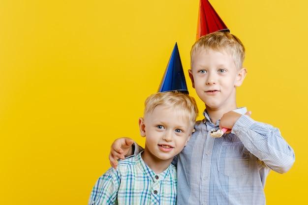 I ragazzi svegli dei fratellini in cappello di compleanno si abbracciano su giallo.