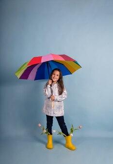 Una graziosa ragazza bruna con stivali di gomma con fiori sta sotto un ombrello multicolore su uno sfondo blu con un posto per il testo