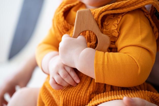 La piccola neonata caucasica sveglia tiene il massaggiagengive in legno. sviluppo iniziale. giocattoli ecologici