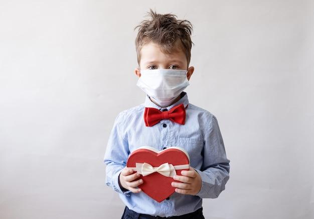 Piccolo ragazzo caucasico sveglio in farfallino con nastro bianco di scatola regalo cuore rosso in maschera. giorno di san valentino. covid.