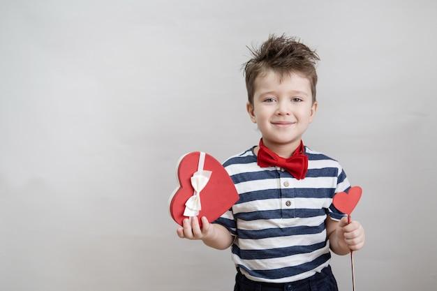 Piccolo ragazzo caucasico sveglio in farfallino con scatola regalo cuore rosso e bianco e cuore di legno sul bastone.