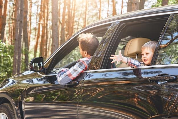 Simpatico ragazzino caucasico seduto all'interno dell'auto e guardando fuori dalla finestra la strada della famiglia