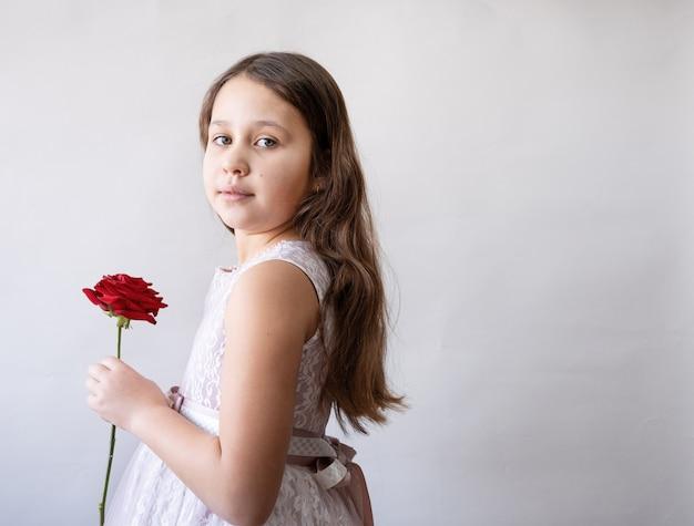 Piccola ragazza caucasica sveglia in bello vestito rosa con rosa. giorno di san valentino.