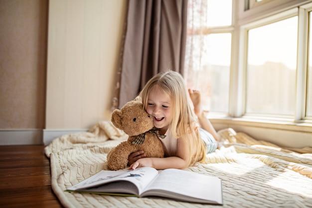 Piccola ragazza caucasica sveglia in vestiti casuali che leggono un libro con il giocattolo dell'orsacchiotto di peluche