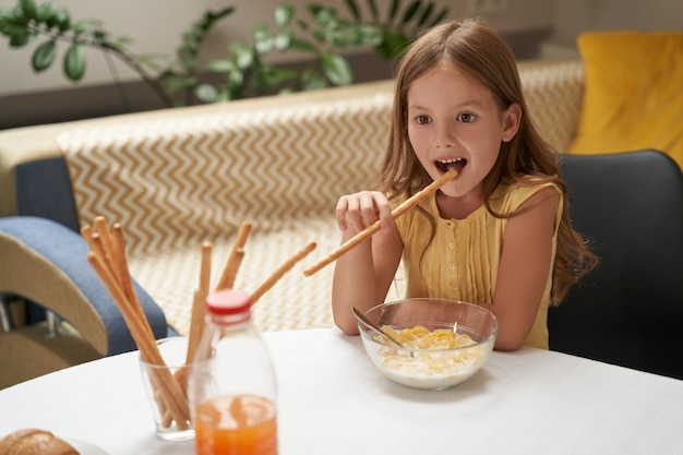 Carina ragazza caucasica che fa colazione a casa e sorride mangiando cereali con latte e snack