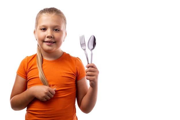 Piccola ragazza caucasica sveglia in una canottiera sportiva arancione che tiene un cucchiaio e una forchetta con un'espressione soddisfatta su un fondo bianco
