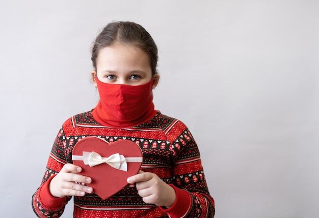 Piccola ragazza caucasica sveglia in vestito rosso con il nastro bianco del contenitore di regalo del cuore in maschera facciale. giorno di san valentino. covid.
