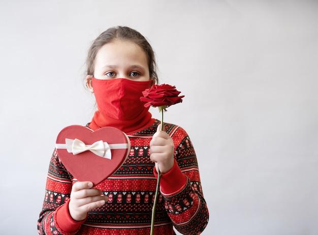 Piccola ragazza caucasica sveglia in vestito rosso con il nastro bianco del contenitore di regalo del cuore e rosa in maschera facciale. giorno di san valentino. covid.