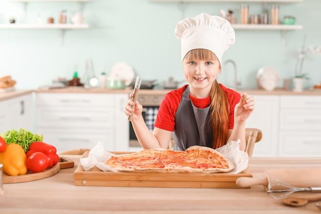 Carino piccolo chef che cucina la pizza in cucina