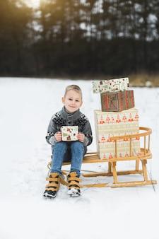 Piccolo bambino sveglio, ragazzo, seduto su una slitta di legno decorata con scatole di regali, tenendo la scatola