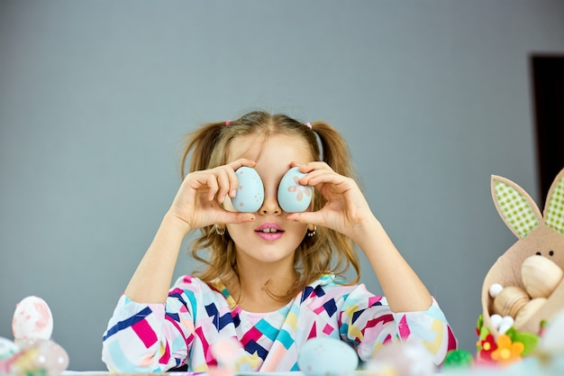 La bambina sveglia del bambino il giorno di pasqua tiene l'uovo di pasqua in mano a casa. ragazza con uova dipinte su sfondo luminoso, buona pasqua