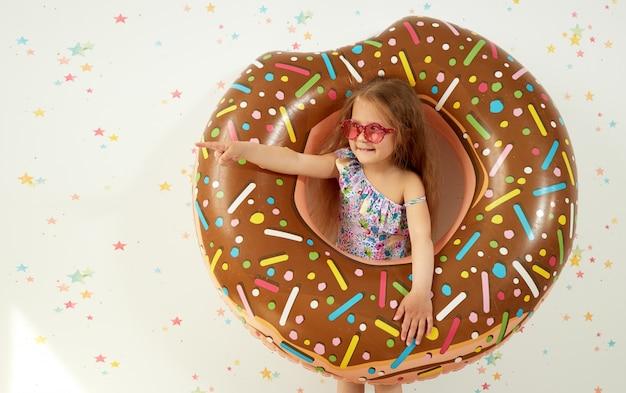 Ragazza sveglia del piccolo bambino in cappello con l'anello gonfiabile sulla parete di colore. quarantena vacanze estive a casa