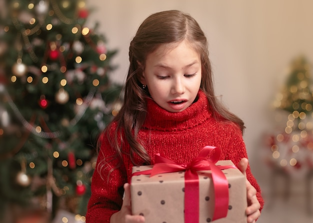 Bambina sveglia del bambino con il contenitore di regalo attuale vicino all'albero di natale a casa.