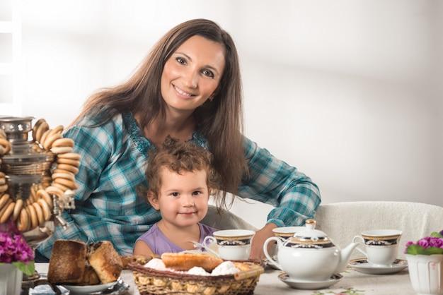 Piccolo bambino sveglio con la madre che si siede al tavolo con i bagel e la teiera