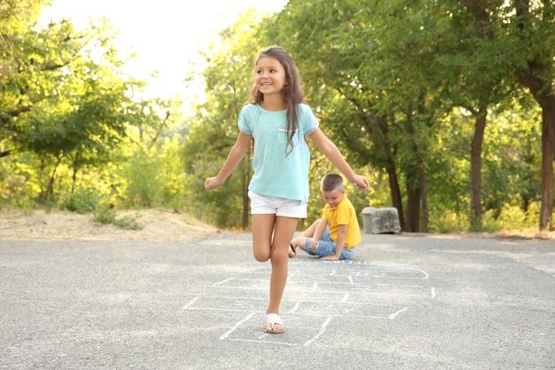 Simpatici bambini che giocano a campana, all'aperto