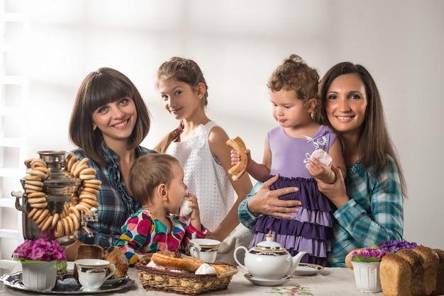 Piccoli bambini svegli con le madri che si siedono al tavolo con bagel e teiera