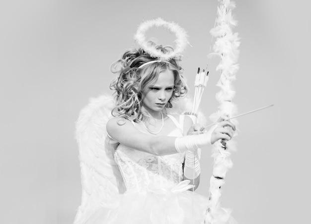 Il piccolo cupido sveglio spara un arco. ritratto di una bambina di cupido. bambina abbastanza bianca come il cupido con un arco e una freccia che si congratula