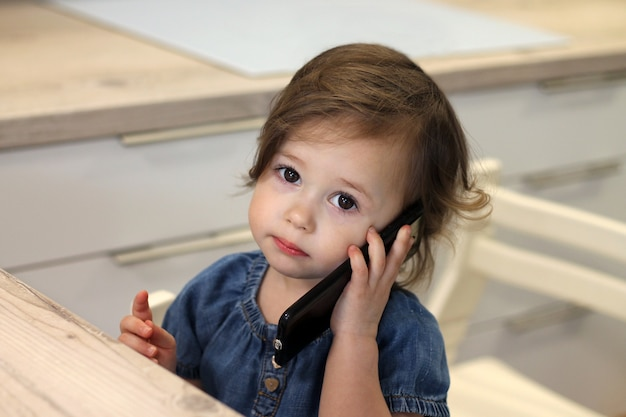 Carina bambina dai capelli scuri 1,5-2,5 in un vestito di jeans sta parlando con qualcuno su uno smartphone in cucina.