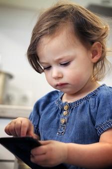 Carina ragazzina dai capelli scuri 1.5-2.5 in un vestito di jeans digita qualcosa o compone un numero su uno smartphone in cucina.