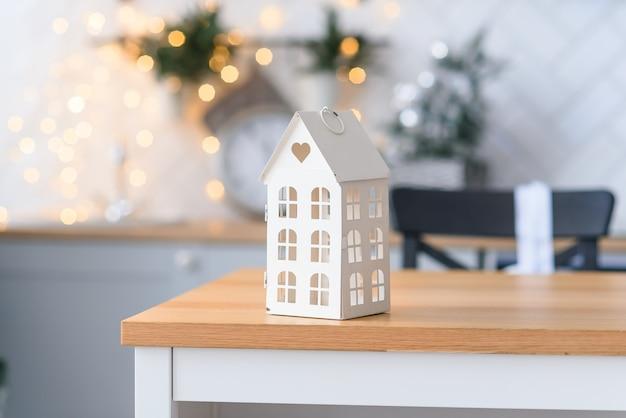 Piccola casa decorativa sveglia sullo sfondo di luci di natale accoglienti. concetto di vacanze invernali.