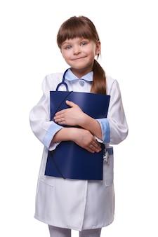 La piccola ragazza sveglia del medico che porta il camice medico bianco con lo stetoscopio tiene la cartella nel fondo isolato bianco