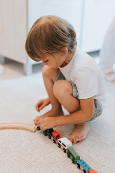 Simpatico bambino di cinque anni con una maglietta bianca che gioca con una ferrovia in legno e trenini sul pavimento sul tappeto nella stanza. i bambini giocano in casa