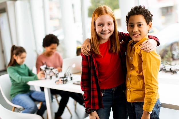 Simpatici piccoli amici in piedi davanti a un gruppo di bambini che programmano giocattoli elettrici e robot in aula di robotica