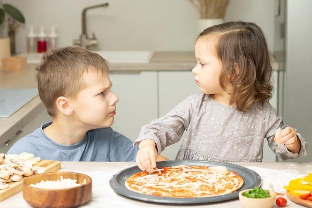 Bambina sveglia 2-4 in vestito grigio e ragazzo 7-10 in maglietta che cucina pizza insieme in cucina. fratello e sorella che cucinano