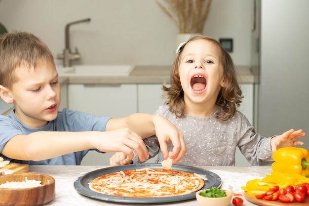 Bambina sveglia 2-4 in vestito grigio e ragazzo 7-10 in maglietta che cucina pizza insieme in cucina