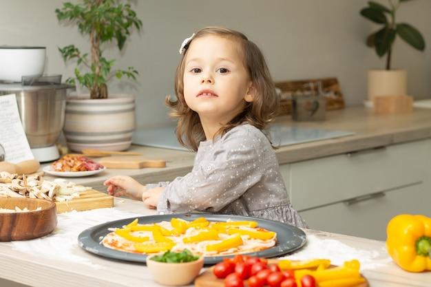 Bambina sveglia 2-4 in vestito grigio che cucina la pizza in cucina. il bambino organizza gli ingredienti sulla base della pizza