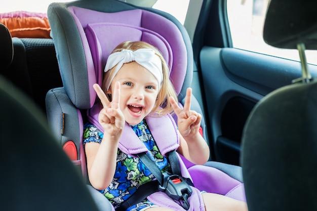 Ragazza carina di 3 anni, ritratto nel seggiolino auto, fissato per motivi di sicurezza, mostra classe