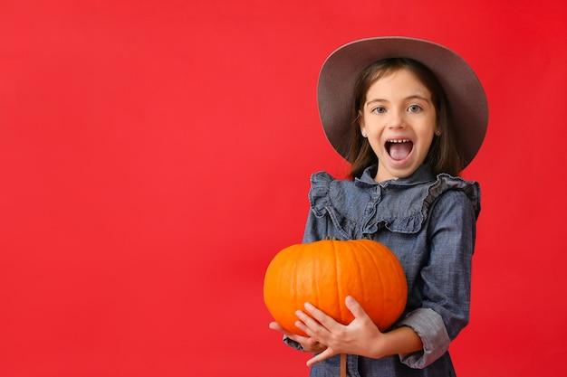 Bambina carina in abiti autunnali e con la zucca sul rosso