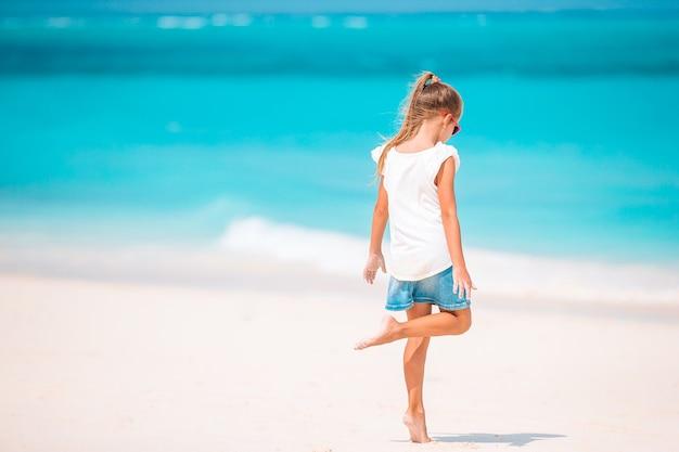 Bambina sveglia sulla spiaggia divertendosi molto in acque poco profonde