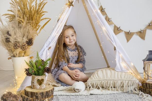 Una bambina carina in un bellissimo vestito gioca in un wigwam a casa. decorazione di capodanno.