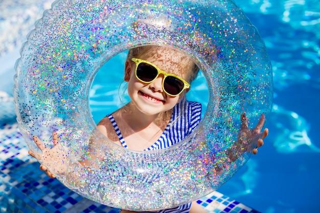 La bionda sveglia della bambina in occhiali da sole ride nella piscina che tiene un'ancora di salvezza