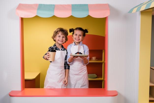 Bambina sveglia e ragazzo che ti danno un bicchiere di bevanda e piatto con torta di bacche o dessert mentre si lavora nella mensa della scuola