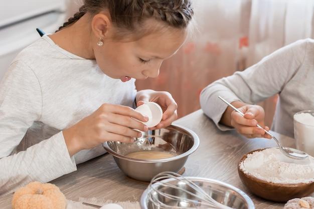 La bambina sveglia rompe un uovo nell'impasto di pan di zenzero per cuocere i biscotti di halloween nella cucina di casa. dolcetti e preparativi per la festa di halloween